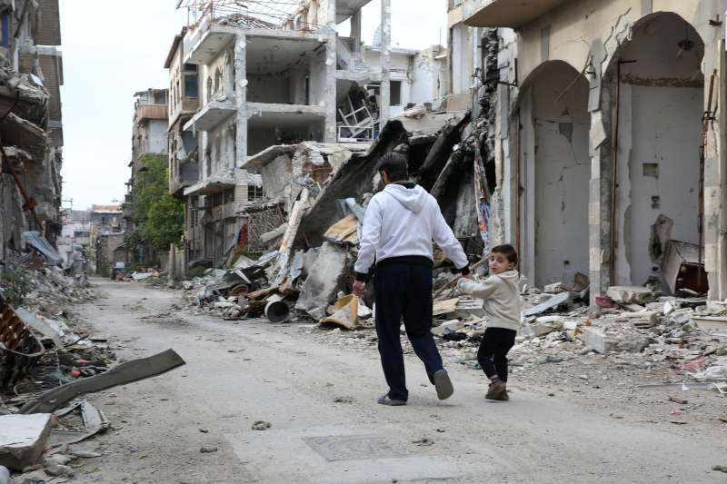 A father and son walk through the ruins of their home town of […]
