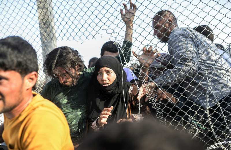 Syrian refugees crowd through broken down border fences to enter southern Turkey earlier this week near the border crossing of Akcakale in Sanliurfa province.