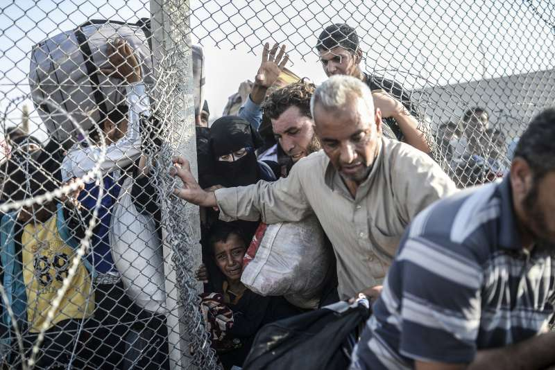 Syrian refugees pass through border fences to enter southern Turkey, near the Turkish border crossing at Akcakale in Sanliurfa province. Thousands more have fled into Turkey in recent days following renewed fighting in Syria from June 3.