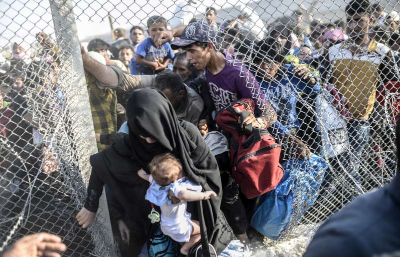 "Syrians fleeing new fighting rush through broken down border fences at the border with southern Turkey. Under an ""open-door"" policy, Turkey has taken in 1.77 million Syrian refugees since the conflict in Syria erupted in 2011."