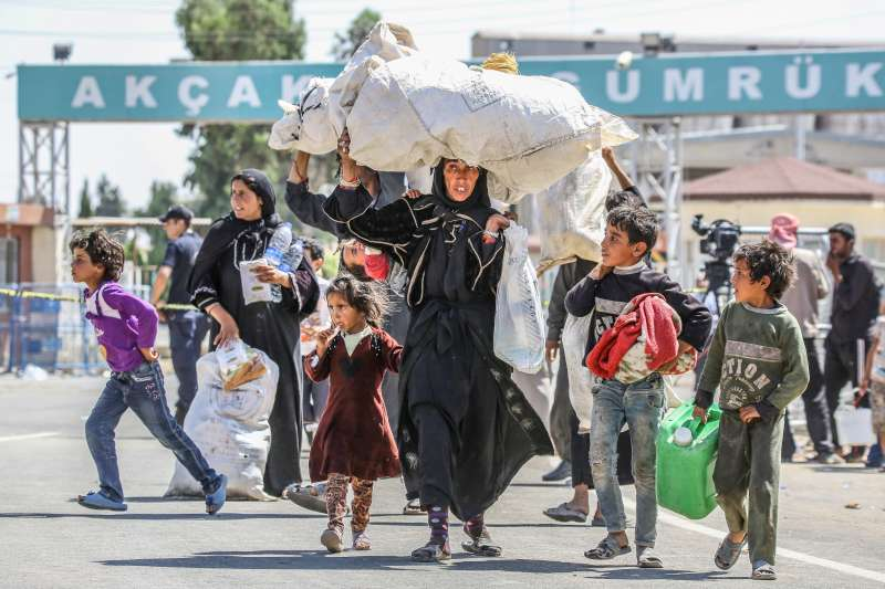 Syrian refugees fleeing fighting in the city of Tal Abyad cross into southern Turkey near Akcakale, Sanliurfa province. Hundreds of Syrians from Tal Abyad, which borders Turkey, have crossed over the border since beginning June 3 when the latest fighting began.