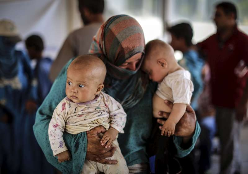 Syrian woman holds two babies in her arms after fleeing crossing the Akcakale border gate in southern Turkey's Sanliurfa province this week.