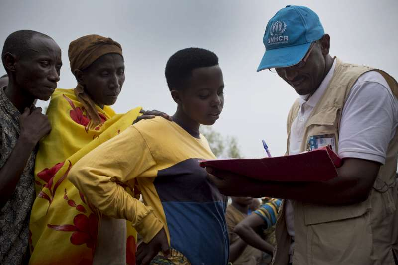 UNHCR staff member Paul Kenya registers refugees from Burundi as they board a bus to take them to the new Mahama refugee camp  in the Bugesera Reception Centre in Rwanda in May.