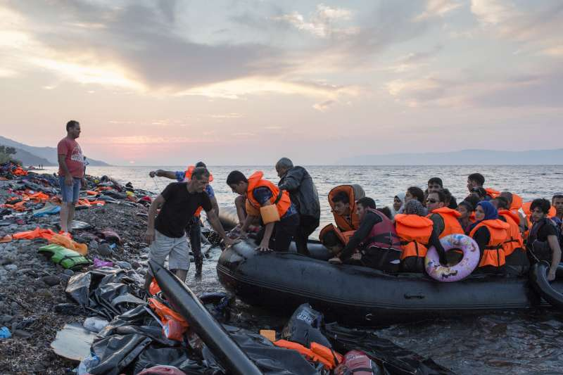 At sunset a group of mostly Syrian refugees arrive on the Greek island of Lesvos after crossing the Aegean Sea from Turkey.