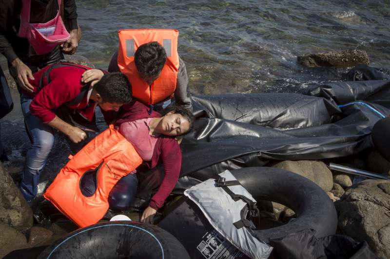 A refugee from Aleppo, Syria, collapses from seasickness and fatigue after the journey from Turkey to Lesvos. She is travelling with her husband and three children.