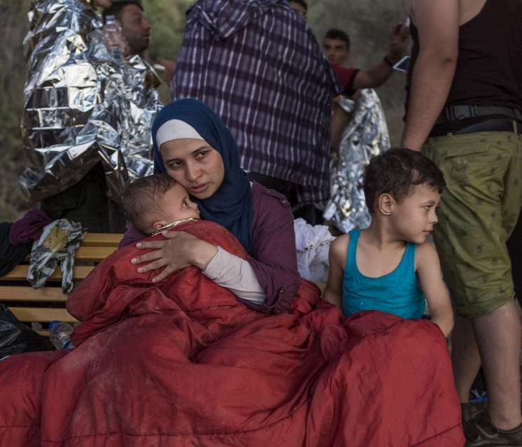 Syrian refugee Asmaa cradles her six-month-old baby, Osman, with her son Abdul-Rahman, 5, close by. Asmaa and her husband, Omar, fled their home near Damascus over six weeks ago, travelling through Lebanon and Turkey before crossing the Aegean Sea to Greece. When its engine cut off, their overcrowded vessel began to take on water. Passengers threw their luggage overboard in a desperate bid to stay afloat. Asmaa's family lost everything, including their passports and what little cash they had.
