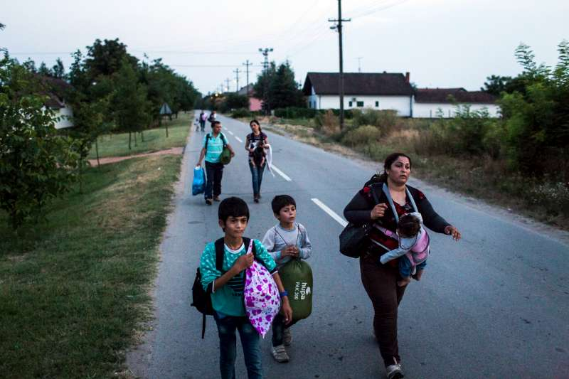In Horgos, Serbia, a mother and her three children walk along a road towards a railway line that will lead them to Hungary.