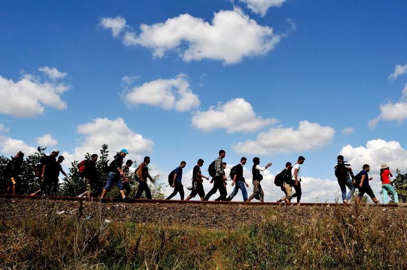 Refugees walk along an old railway line, just after crossing from Serbia into Hungary.
