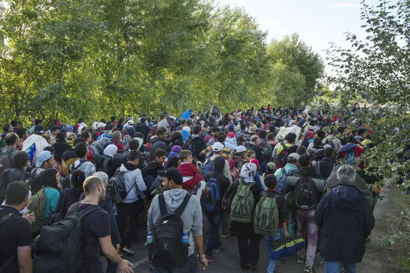 "In Hungary, newly arrived refugees and migrants are accompanied by police on the road to the registration centre. Many had hoped to continue on from the border to Budapest and were chanting, ""Budapest, Budapest..."""