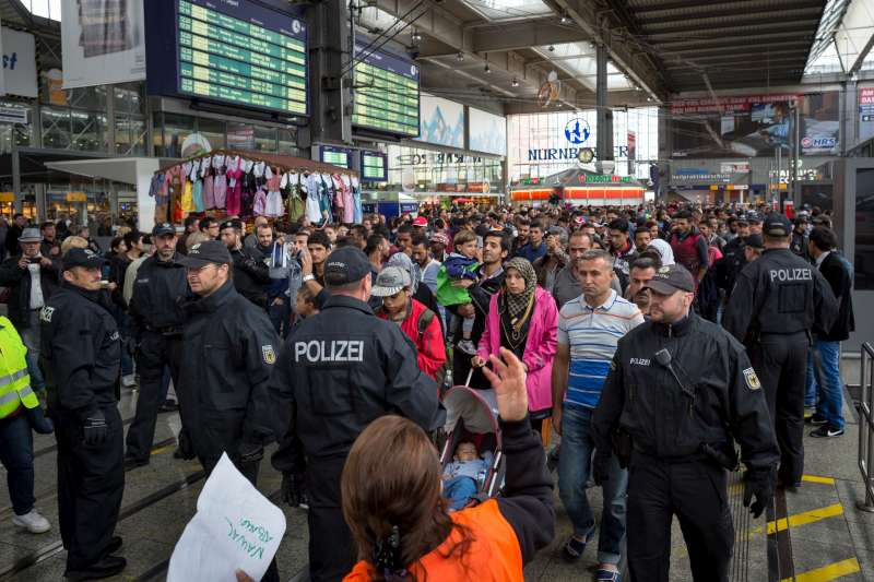 A train filled with refugees and migrants arrives in Munich's central station on platform 17. Police escorted new arrivals to an area set up for medical checks.