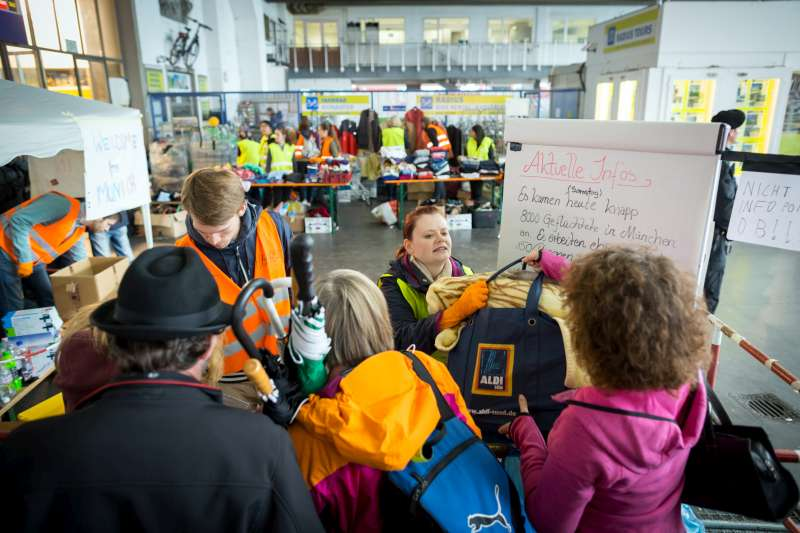 Local volunteers in Munich hand out bags filled with practical items to refugees and migrants arriving at the train station.