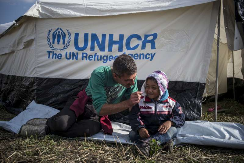 Mahmoud, a Syrian refugee from Aleppo, plays with his son Jawad, 4, in front of their tent in Hungary.