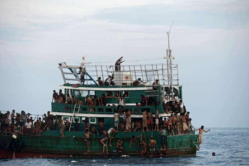 Refugees gather supplies airdropped to a fishing boat adrift in the Andaman Sea.