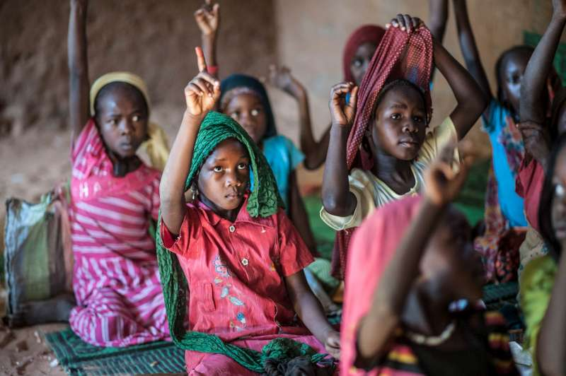 Child refugee Zoera, in faded red dress with green headscarf, attends class at Djabal camp in Chad