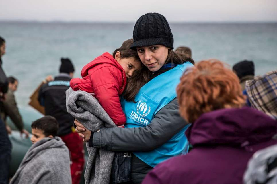 A UNHCR staff member comforts a young refugee boy after his boat landed on the Greek island of Lesvos.