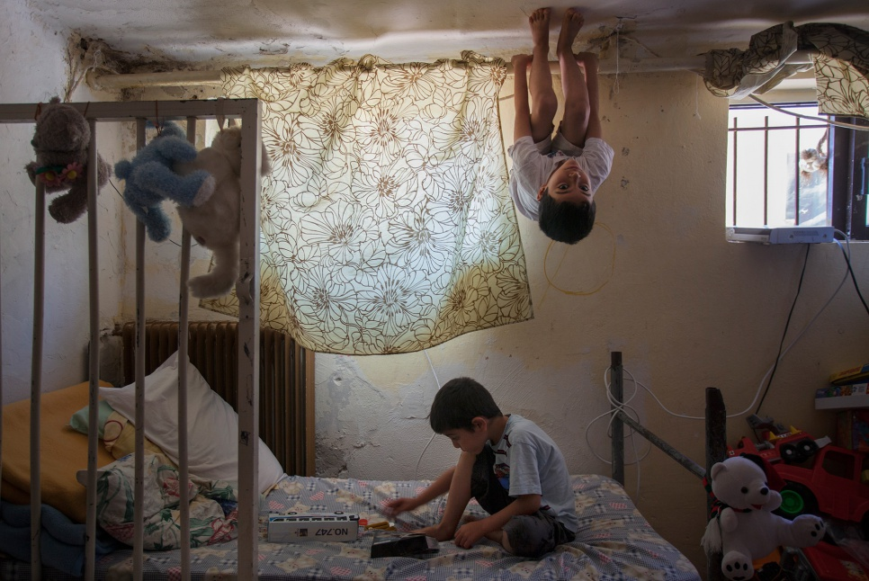 Mohammad and Ahmed play in the single room they share with their mother. Greece's dilapidated Lavrion camp has been their home for six months.