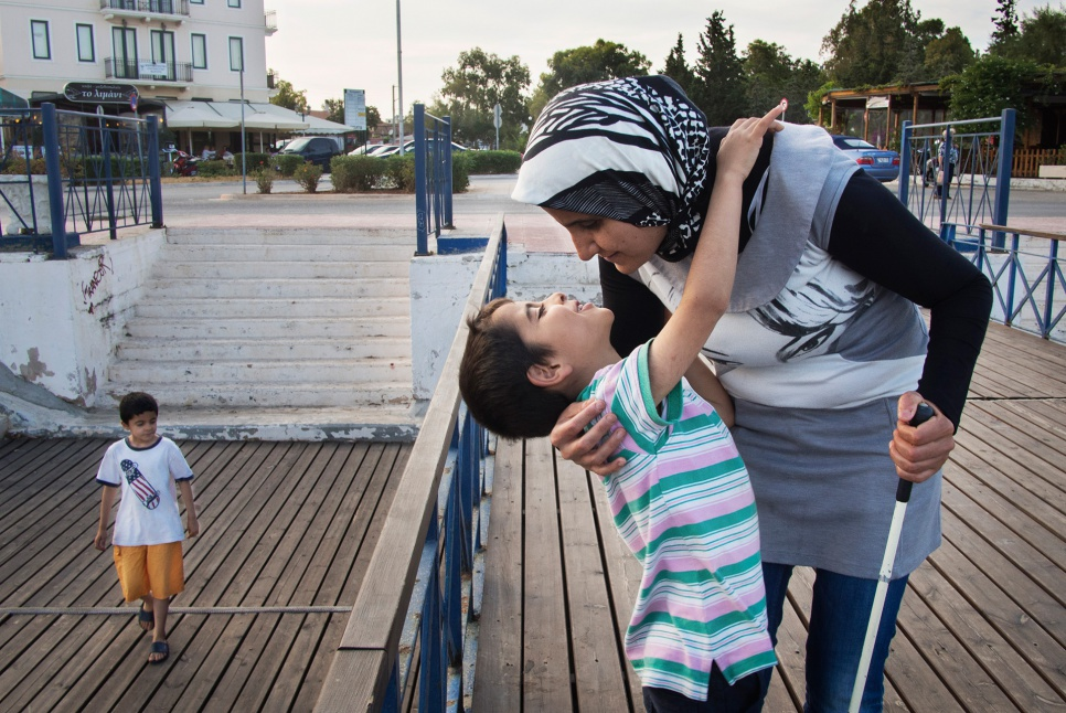 Jihan embraces her younger son, Ahmed, while Mohammad strolls along the boardwalk by the harbour in Lavrio. Their rundown camp is a world away from the picturesque tourist town.