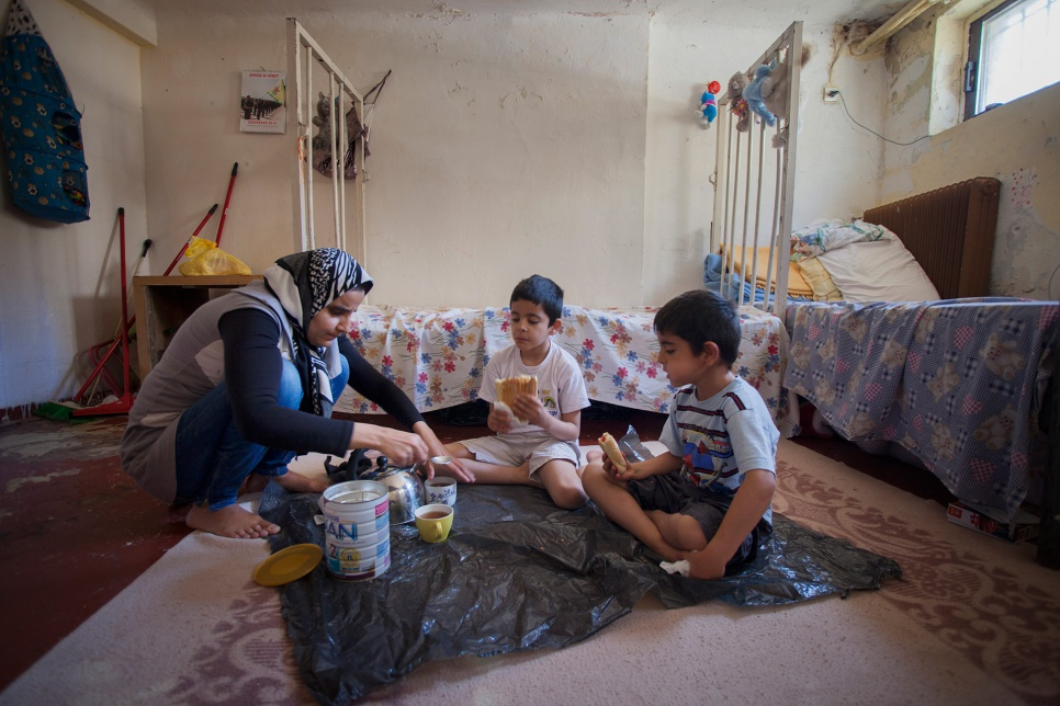 Jihan and her sons eat breakfast on the floor of their one-room home. Back in Syria, she and her husband had good jobs and high ambitions for their children's education.