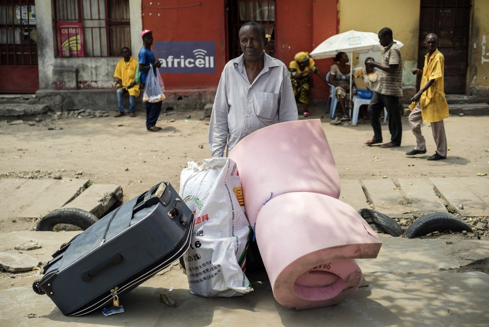 Theophile, 66, waits for assistance with his luggage at a collection point in Kinshasa, DRC. After decades in exile, he is finally going home.