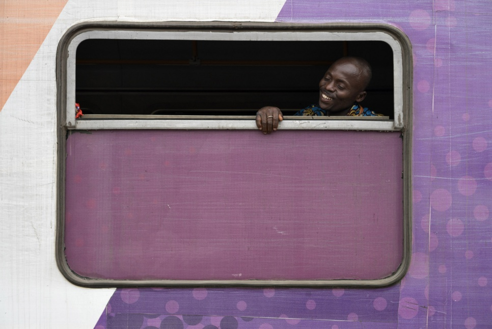 A former Angolan refugee looks out the window of a train on the platform at Kinshasa Est station in DRC. Soon, he will begin his journey home to Angola.