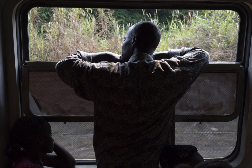 A former refugee looks out the window of a train as it travels from Kinshasa, DRC, towards his home of Angola. Nearly 500 others are travelling with him.