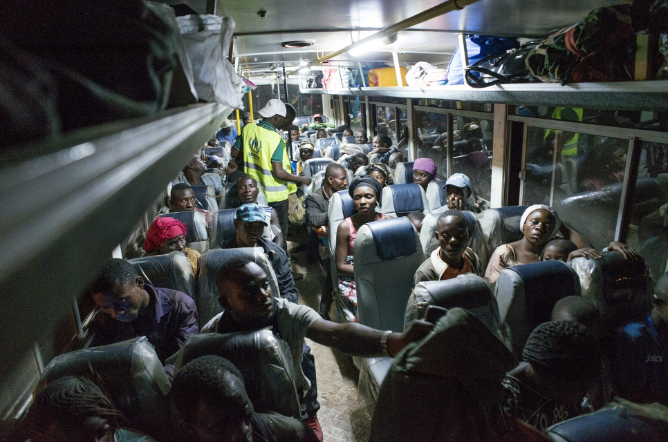 After having their documents verified by Angolan authorities, former refugees wait on a bus before leaving Kimpangu, DRC, for the nearby Angolan border.