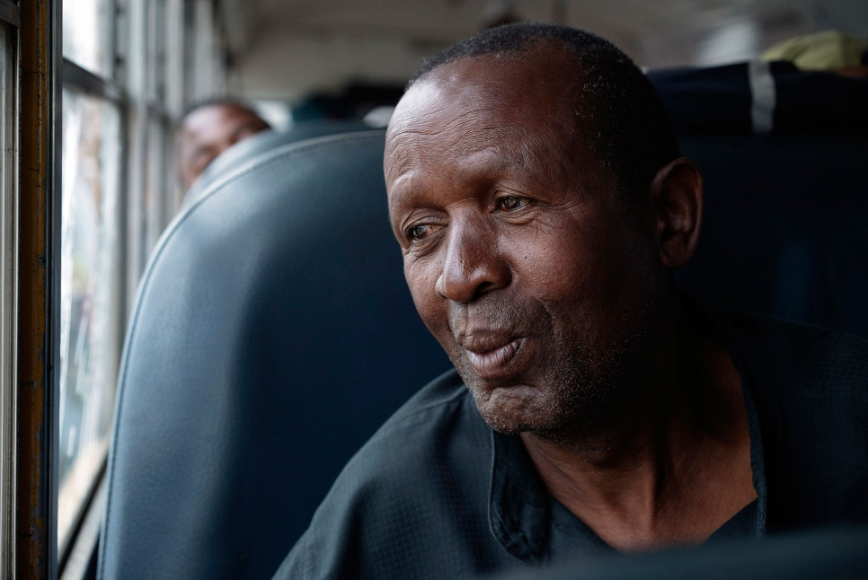 Theophile, 66, sits aboard a bus on his way home to Angola. After decades in exile, he has mixed feelings about leaving the community that gave him refuge.