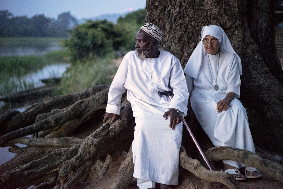 Imam Moussa Bawa, 72, and Sister Maria Concetta, 80, discuss their hopes for the future on the banks of the Oubangui river in Zongo, Equateur Province, DRC.""