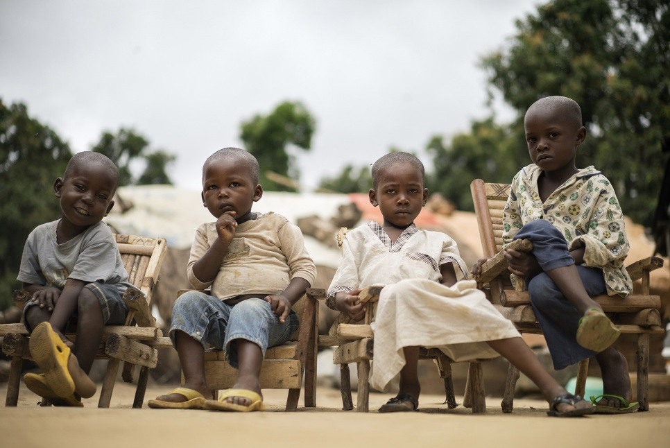 The children of Muslim Central African refugees sit in small wooden chairs at the home of Imam Moussa Bawa while their parents discuss reconciliation in Zongo, DRC.