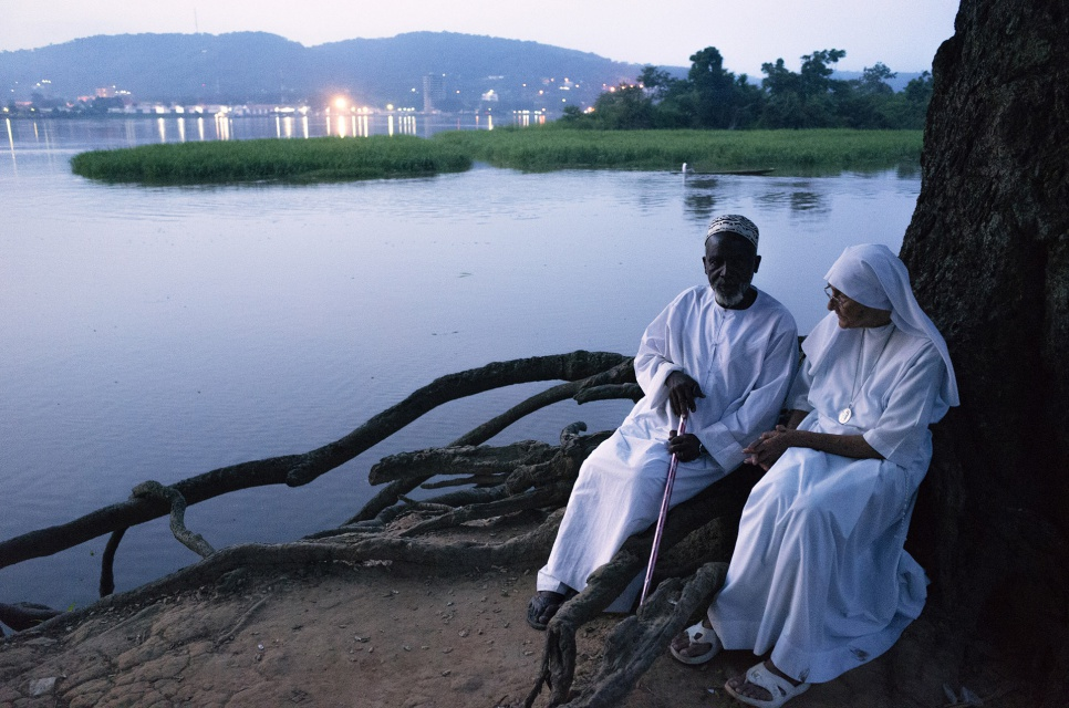 Imam Moussa Bawa and Sister Maria Concetta sit by the banks of the Oubangui river in Zongo, DRC. Across the river the lights of Bangui can be seen.