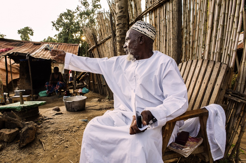 As the sun sets, Imam Moussa Bawa, 72, gestures toward his home in Zongo, Equateur Province, DRC. He was born in nearby Libenge and has lived in Zongo for 34 years.