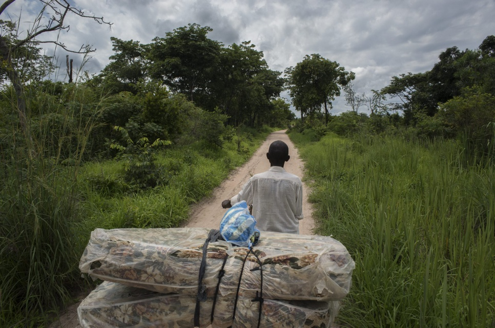 Vincent pushes a bicycle carrying his mattress along the road in Katanga Province. He fled from Kamala to Manono following clashes and is among the first residents to return.