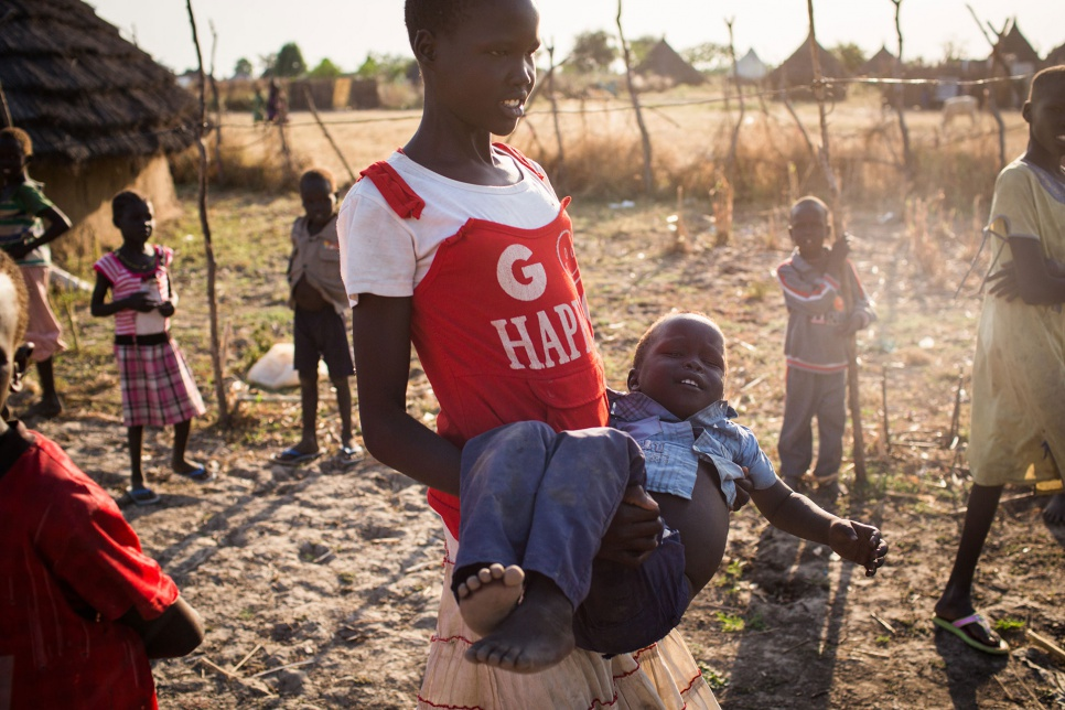 "Lina carries three-year-old Dongwei in Pariang, South Sudan. ""Do I play – No, I do not have time."""