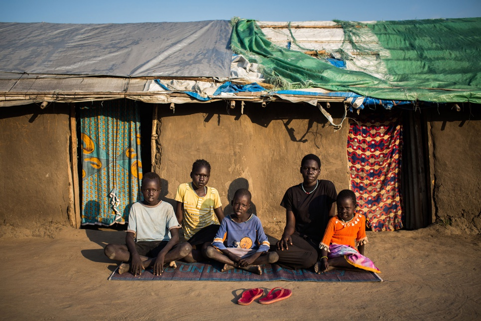 Adut (in black) sits with her younger siblings outside their temporary shelter in Bor, South Sudan.