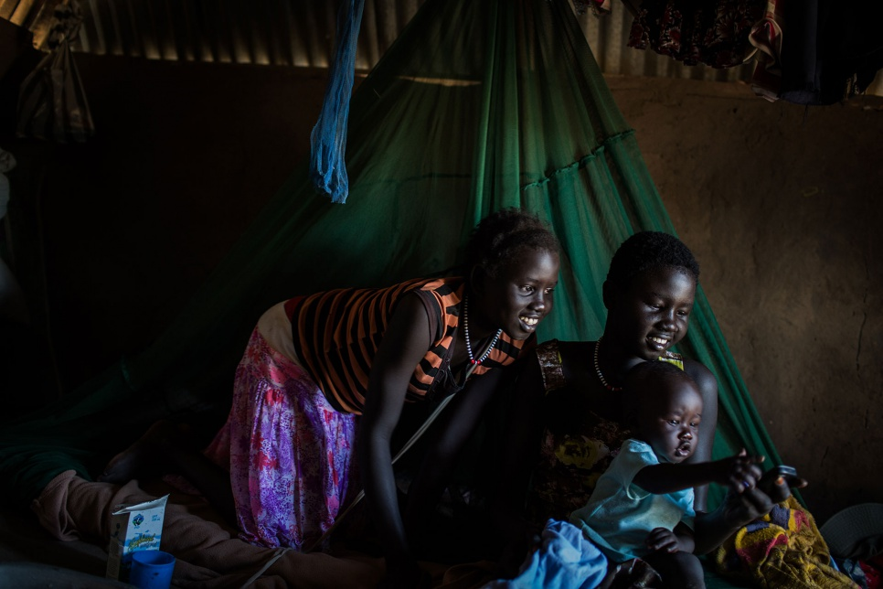 "Sisters Amol and Deborah play with their eight-month-old nephew, Nak, in Bor, South Sudan. ""I don't know what happened [to our mother], but I know we have to look after ourselves."""