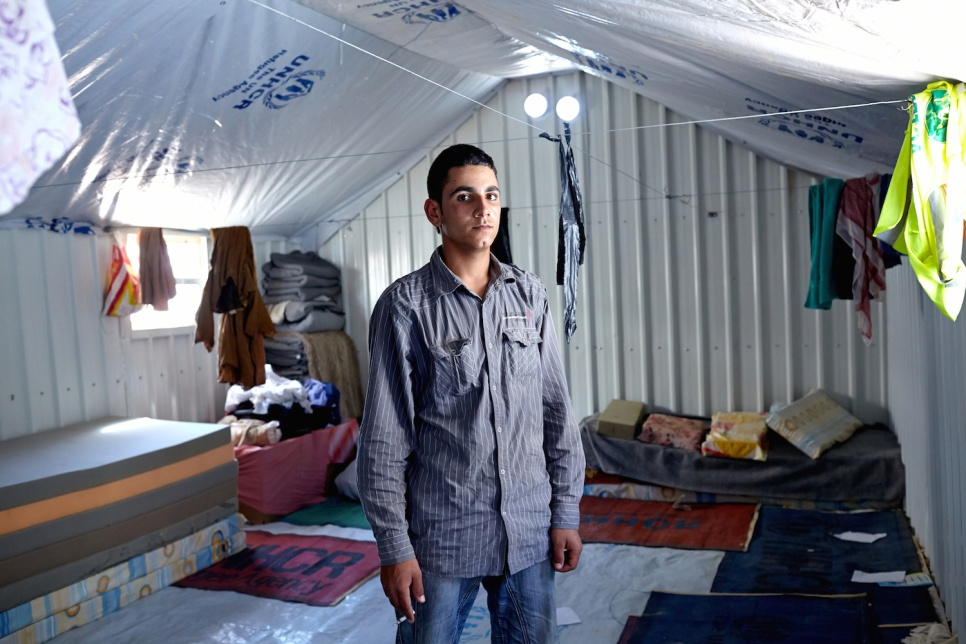 "Amer, 20, inside his family's shelter at Azraq camp. ""With outside light we could gather more easily and talk with friends and family. Being able to socialize helps you feel better."""