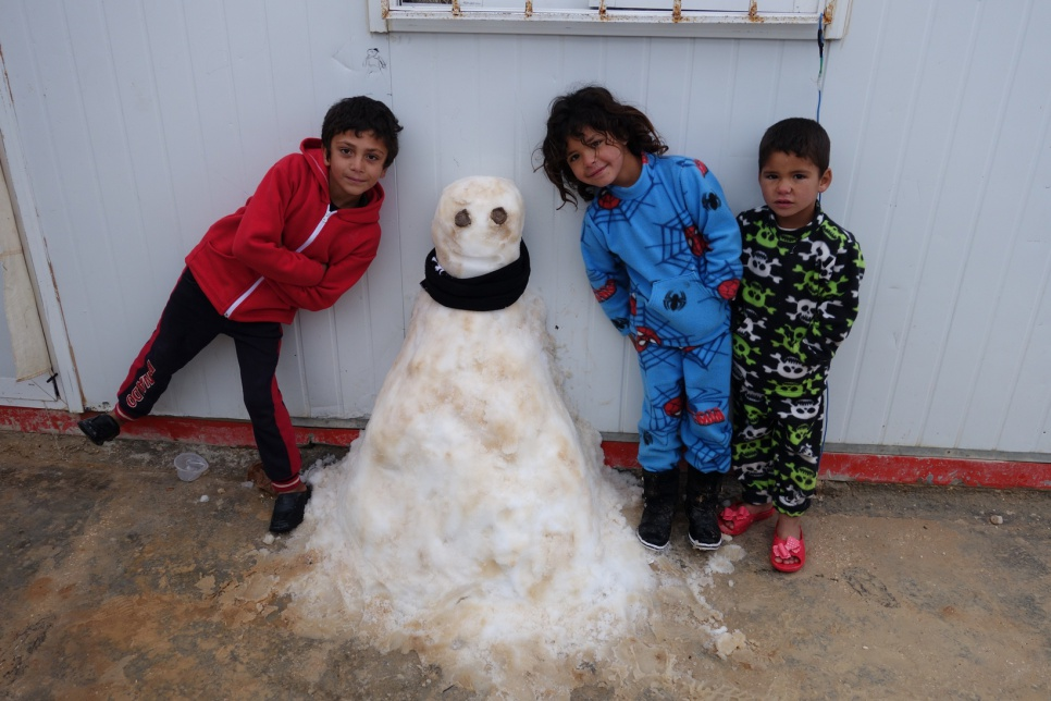 Syrian refugee children pose with a snowman they sculpted at Jordan's Za'atari refugee camp, as the winter storm rages on.