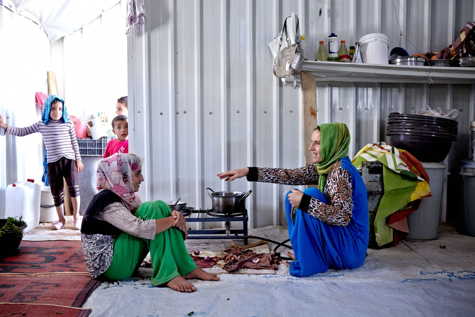 As children look on, Amer's sister, Bushra (left), and mother, Mona (right), prepare a meal in their shelter at Azraq camp in Jordan.