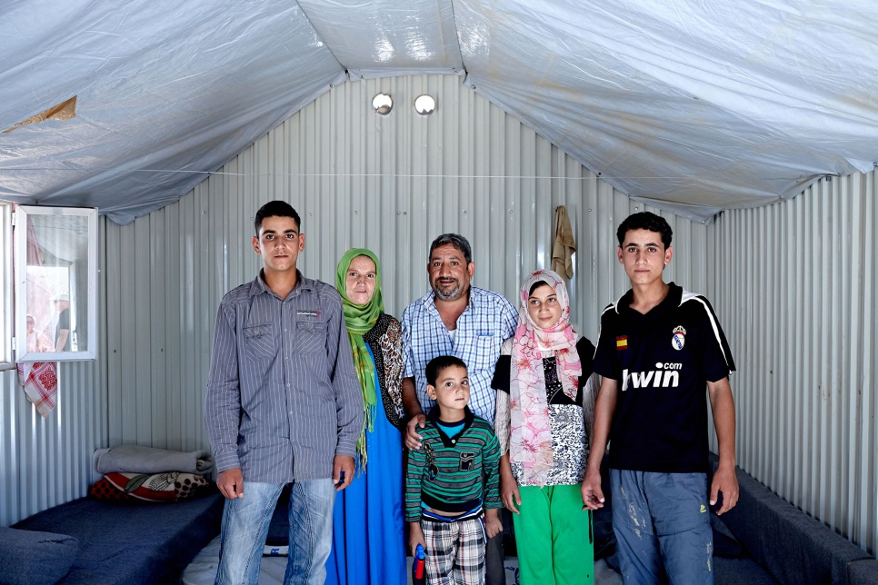 "Amer (left) with his parents and siblings in their shelter at Azraq refugee camp in Jordan. ""When we don't have proper light, the shadows play games and you imagine the worst."""