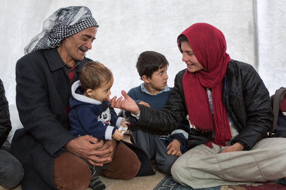 Wazzam and Ayesha play with their youngest child inside their new tent in Suruc camp in Turkey.
