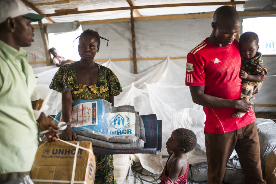 Souzane collects sleeping mats, blankets and a mosquito net at Bili camp while her husband carries their youngest child and a sibling looks on.