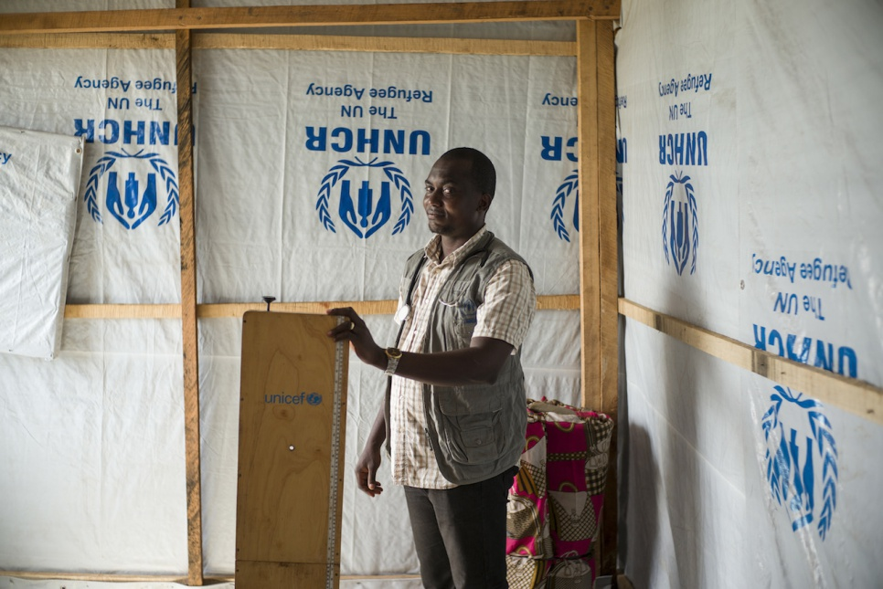 At the mobile health clinic in Congo's Bili camp, Dr. Tony Mayawula holds a scale for weighing refugees and helping to assess their condition.