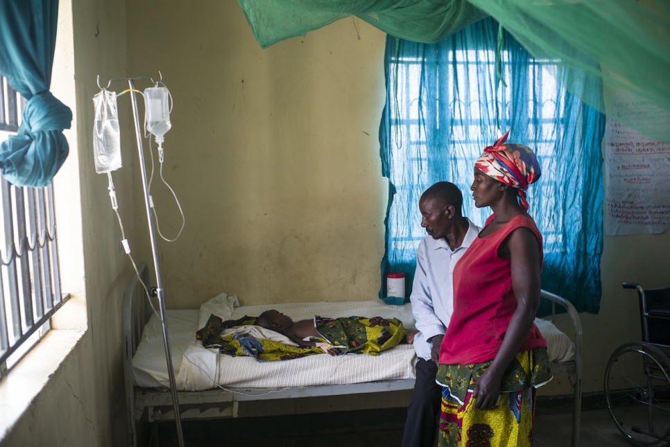 Janette and John watch over their 18-month-old daughter, Agness, who has been diagnosed with malaria.