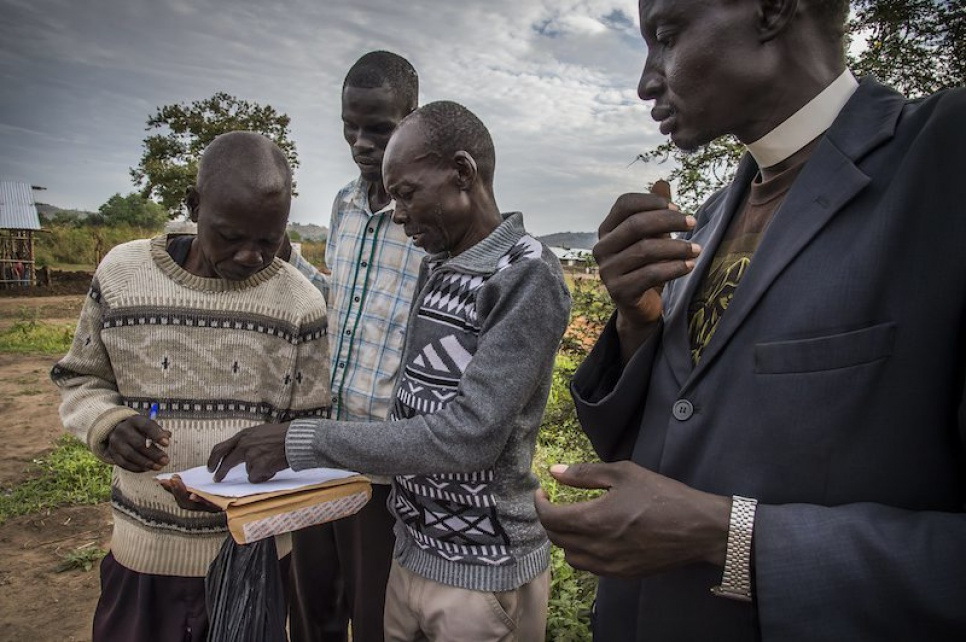 Peter Kenyi, a local landowner, signs a document with a local government official to hand over the rights to his land so that Alaak can expand the school.