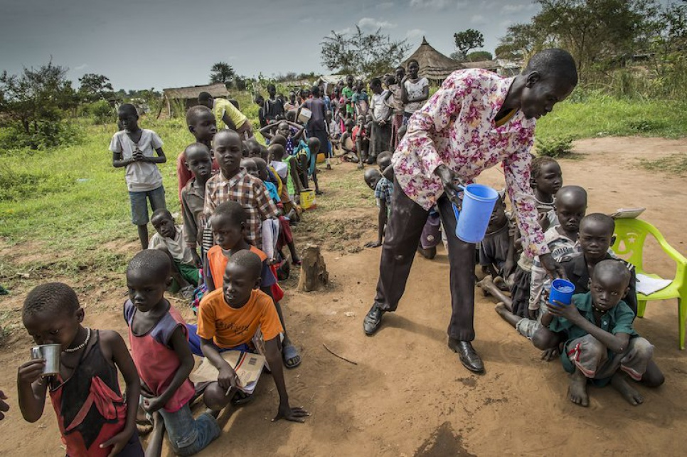 Alaak distributes water to his students during a break from class at Uganda's Nyumanzi refugee settlement.