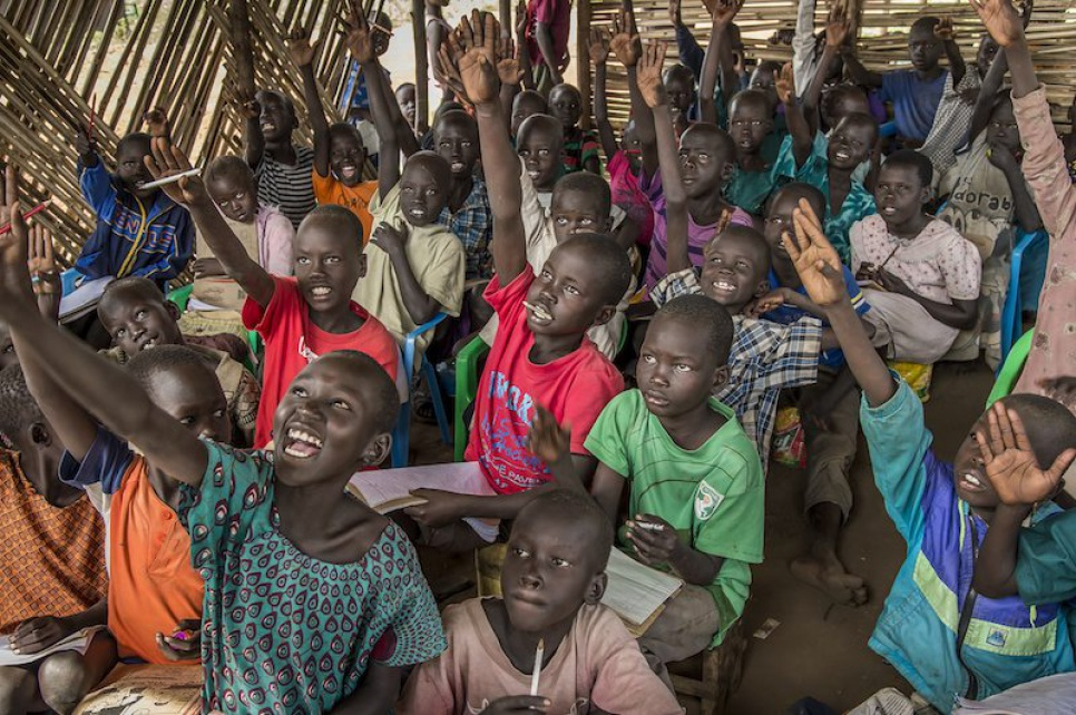 Refugee children from South Sudan eagerly raise their hands to answer Alaak's question.