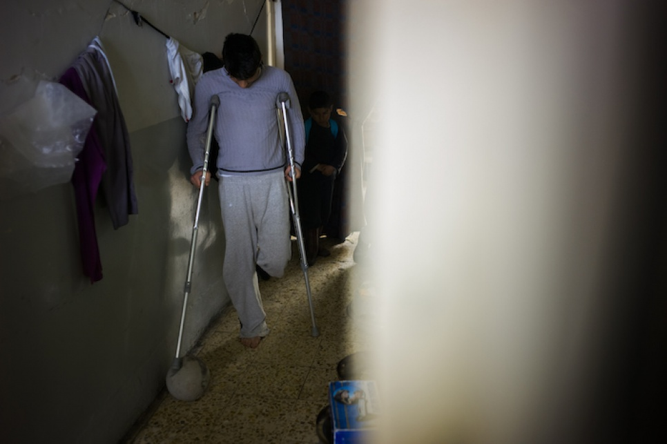 Asam plays with a football in the corridors of the temporary accommodation in Amadi, where he and his family have found refuge after fleeing attacks on Sinjar, Iraq.