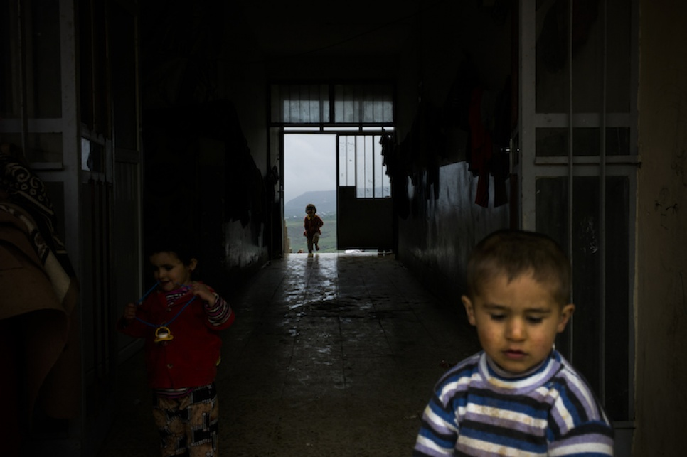 Young Yazidi children run around inside their temporary accommodation in Amadi, in northern Iraq, after fleeing fighting in Sinjar.