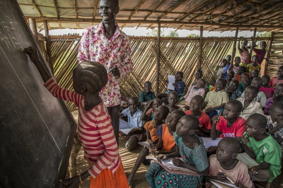 Alaak leads a math class for young refugees at Nyumanzi settlement in Adjumani, Uganda. He and a volunteer, his cousin John, teach 500 students each day.