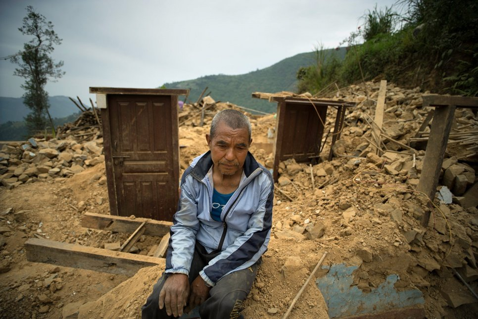 Dhan Bahadur Tamang sits amid the ruins of his home in Jhankridanda village, which collapsed during the earthquake last month in Nepal.